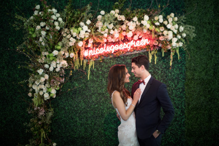 Hedge Background with Rustic Flowers and Neon Sign at Wedding