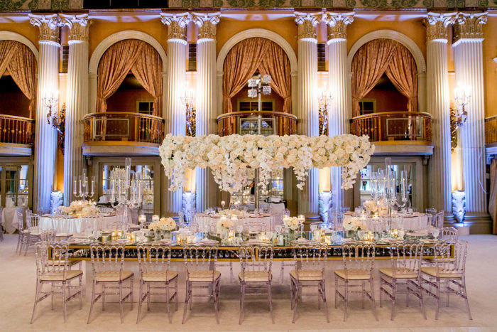 Wedding bridge centerpiece with white flowers and orchids and Clear chairs