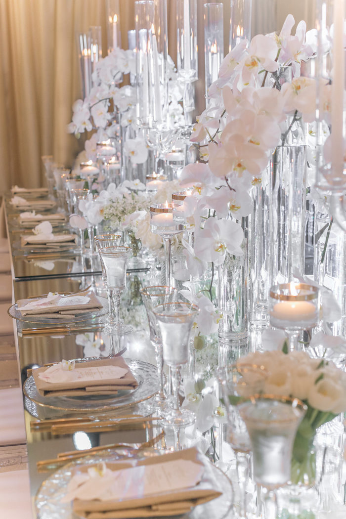 Clear glass candles with white orchids at wedding