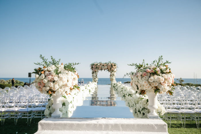 Mirror catwalk with large urn pieces at wedding ceremony