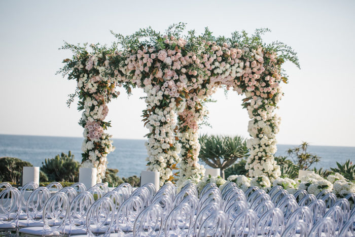 Blush pink and white chuppah with greenery in front of clear louis chairse