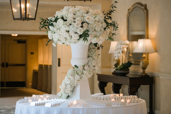Stunning wedding escort table with urn piece and cascade of roses down the urn