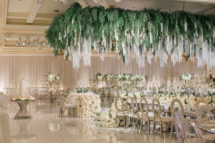 Large greenery orchids and crystals hanging down from ceiling at wedding reception