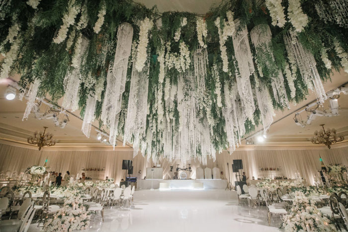 Orchids greenery and crystals hanging down from ceiling at wedding reception