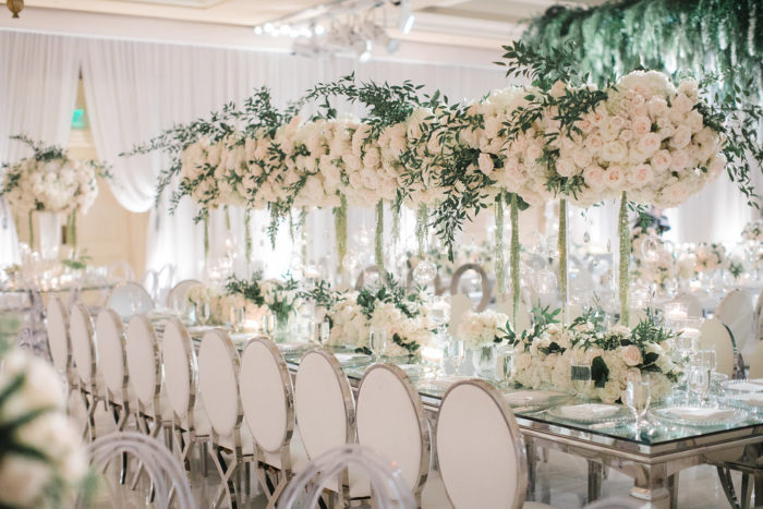 White louis chairs with mirrored table and white florals at wedding reception