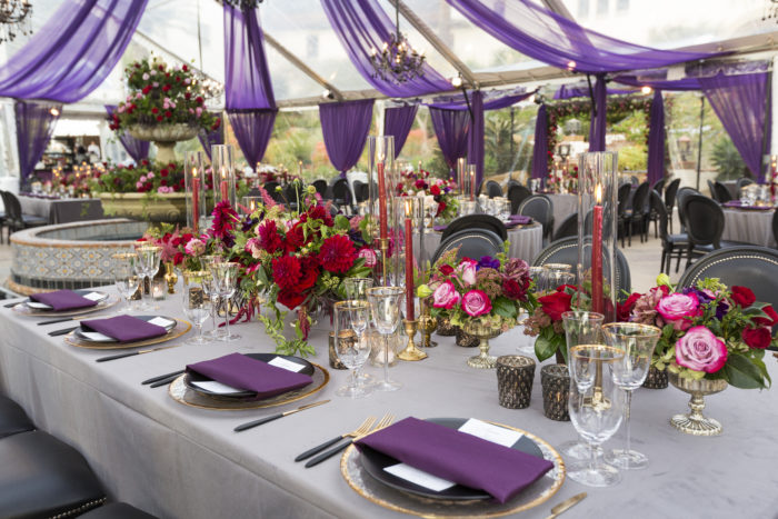 Wedding place setting with red candles red flowers and purple napkins