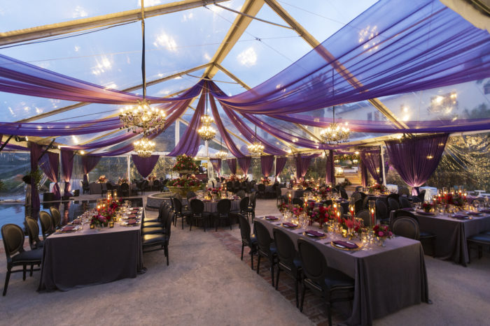 Wedding Tables and upholstered chairs under tent at Hummingbird Nest Ranch Villa