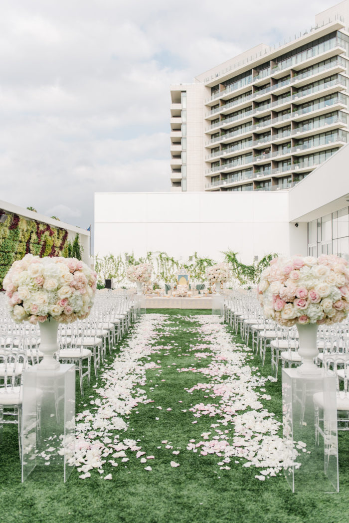 Ceremony aisle urn centerpieces in pink on top of acrylic pedestals