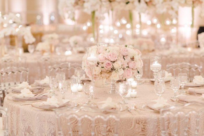 Low centerpieces in crystal compote at neutral pink wedding