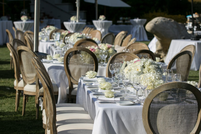 White linens and rustic chairs at outdoor wedding reception on Waterfall Lawn