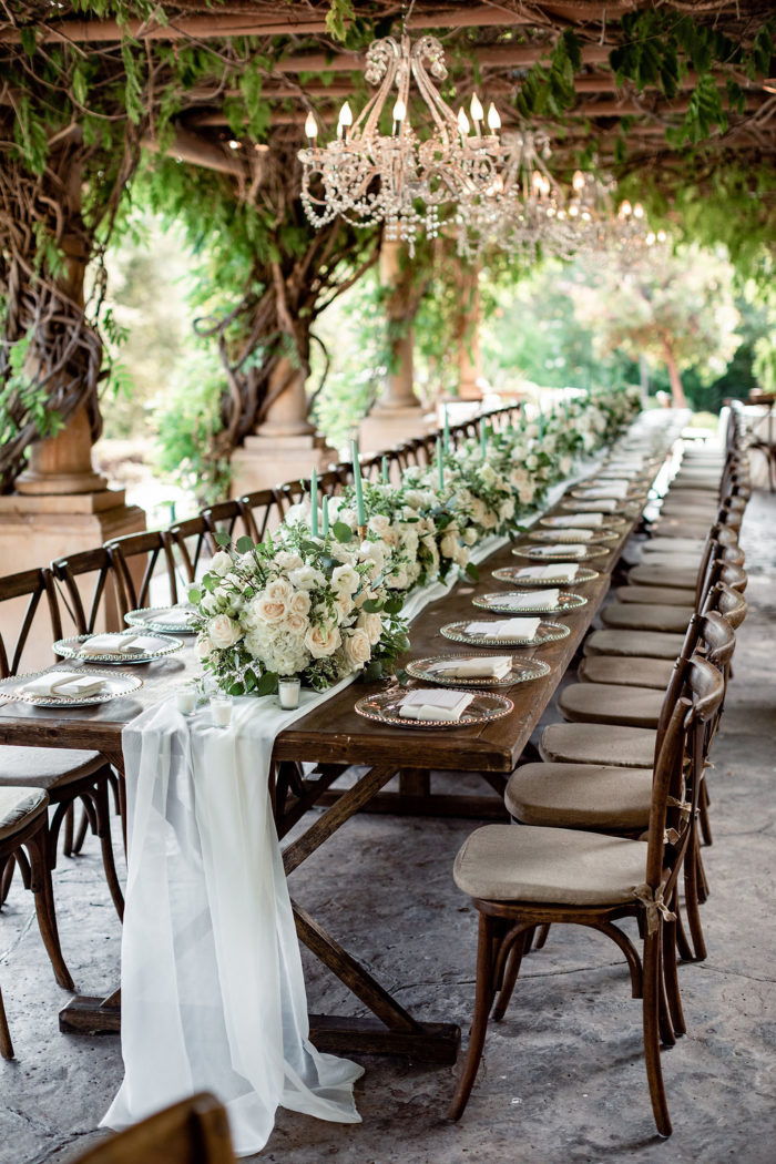 Cross back chairs and gold chargers at a rustic wedding
