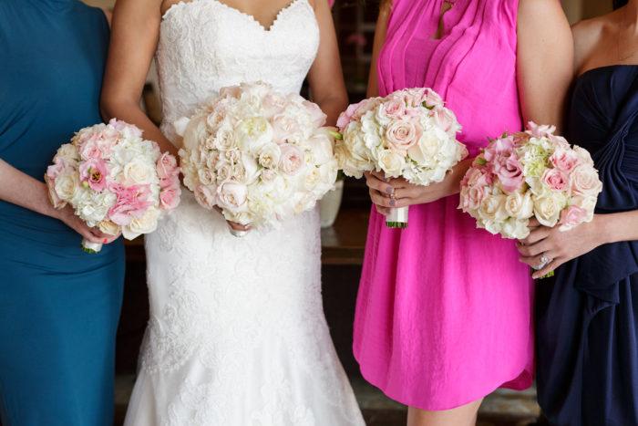 Mismatched bridal party dresses with blush bridesmaid bouquets