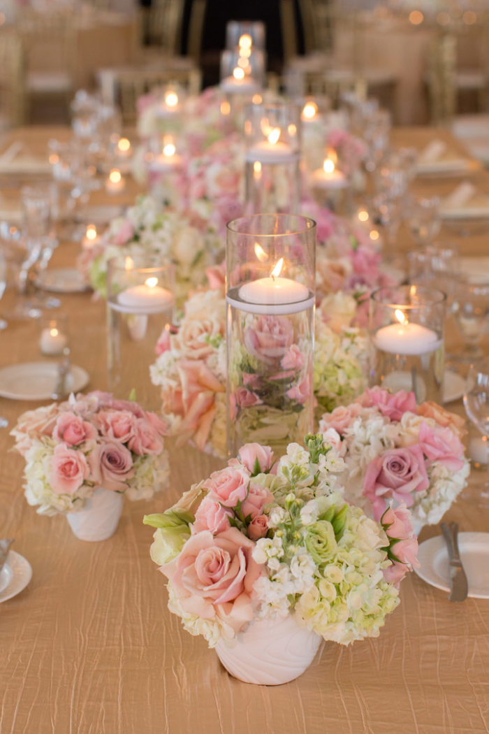 Candles in hurricane with pink and blush flowers at wedding reception