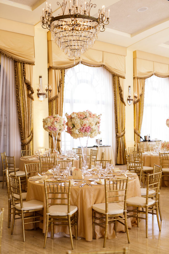 Tall blush pink wedding centerpieces with gold at Riviera Country Club