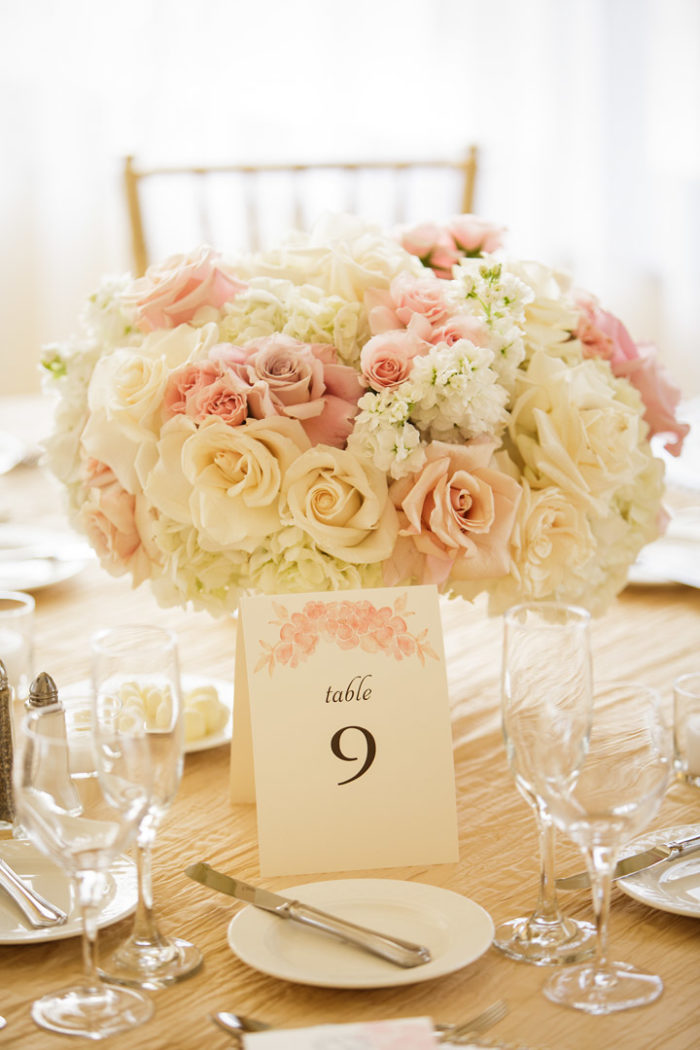 Low wedding centerpiece with blush peach and pink florals and table number card