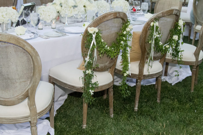 Greenery on bride and groom's chairs in wedding reception Decor