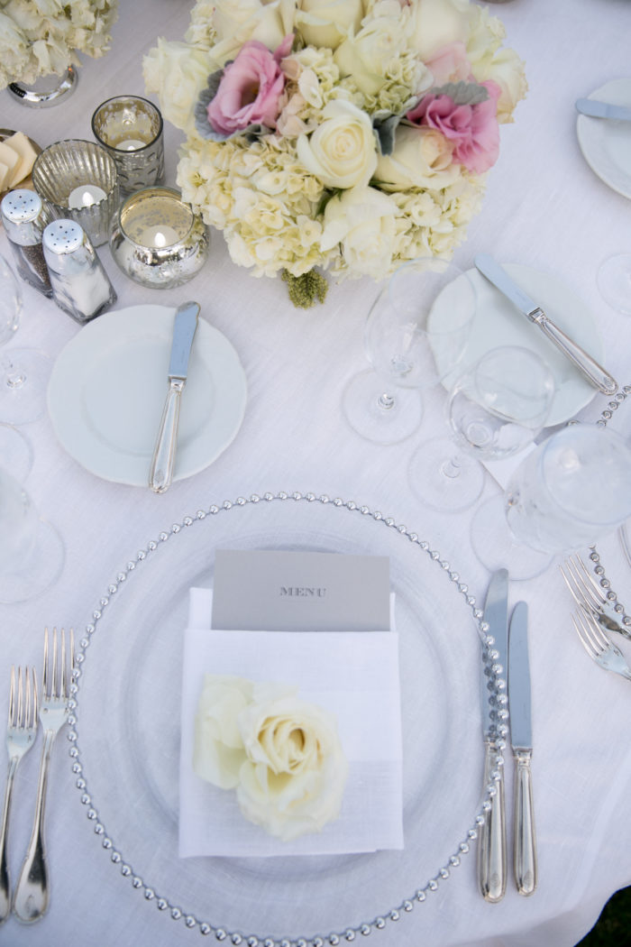 Table setting at wedding with rose bloom and folded napkin with gray menu