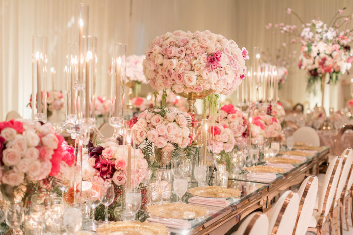 Collection of pink, blush and hot pink centerpieces with roses and greenery