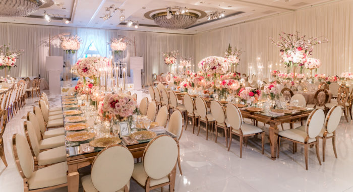 White glossy dance floor with white rental chairs and rose gold tables