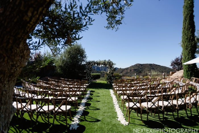 Rustic wedding ceremony with white flowers and crossback chairs at Cielo Farms
