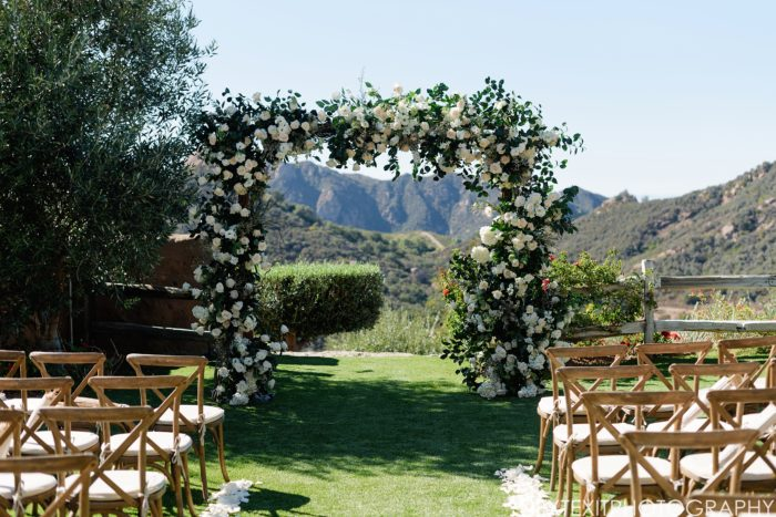 Rustic wedding Chuppah with white roses and rustic greenery