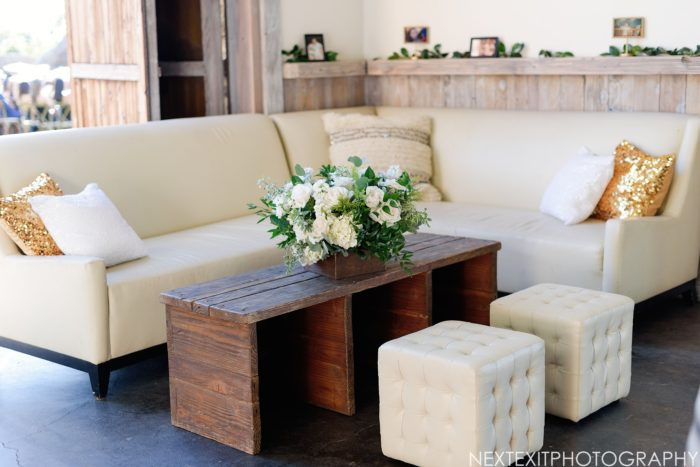 Rustic wedding lounge set at cielo farms with white ottomans and sofas