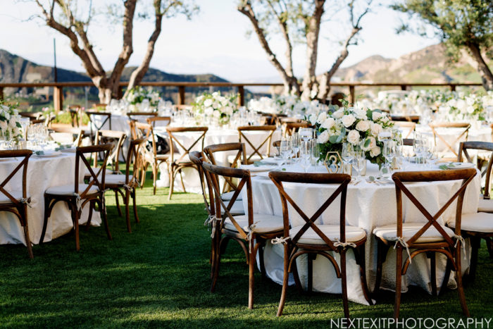 Wedding Reception with crossback chairs and rustic centerpieces at Cielo Farms