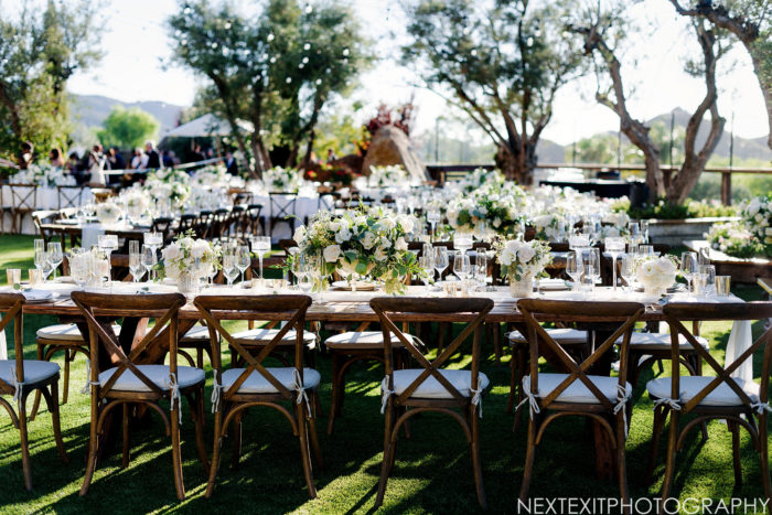 Rustic wedding reception with wood tables and crossback chairs at Cielo Farms